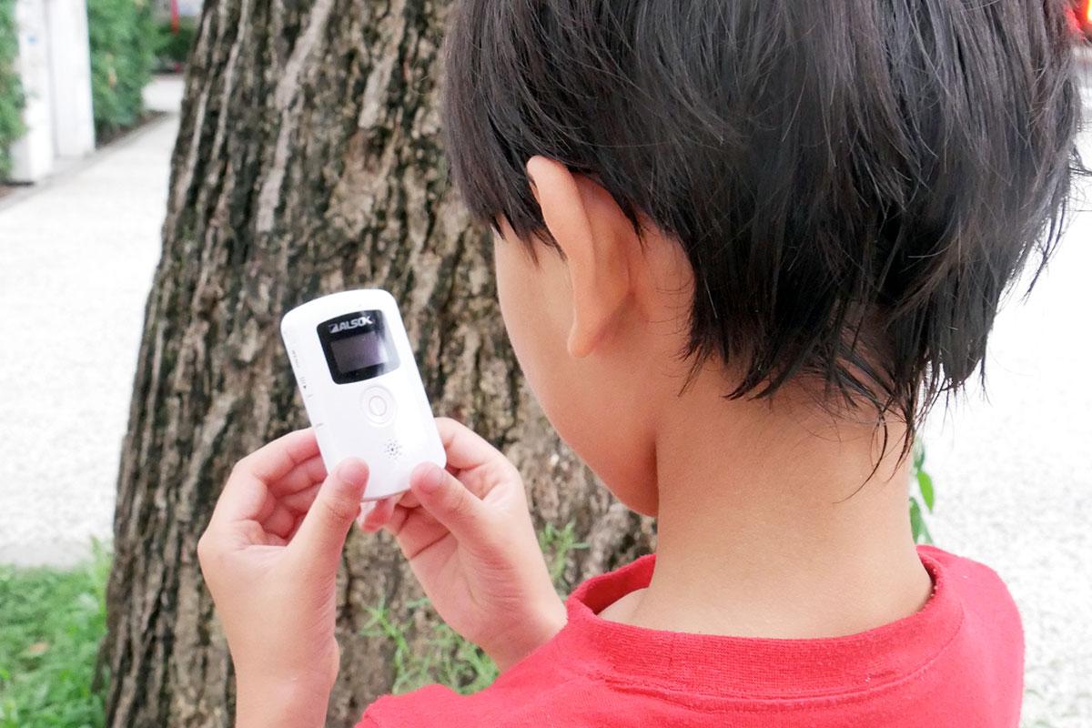 小学生の子どもがALSOK「まもるっく」を持っている場面